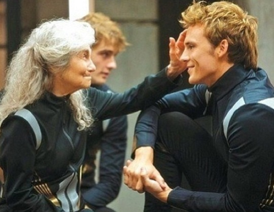 Mags' running her hand through Finnick's hair in THE HUNGER GAMES: CATCHING FIRE